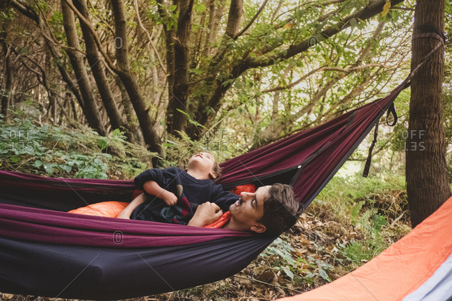 A man and a young kid lying in a hammock in the forest