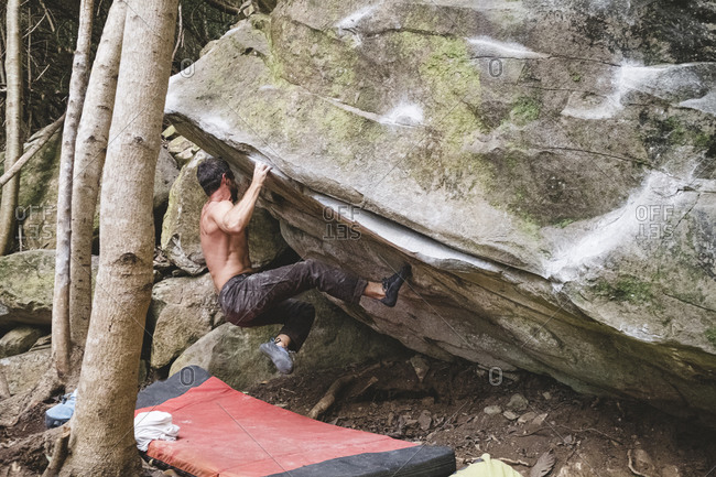 A male rock climber climbs a rock outdoors