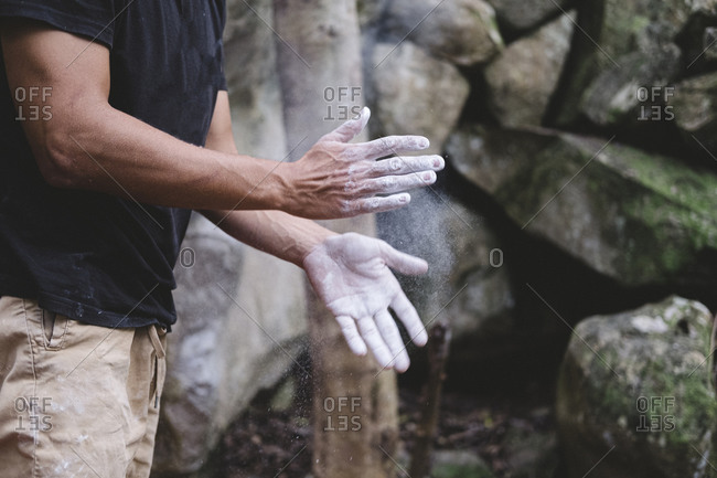 Close up of climber hands clapping chalk