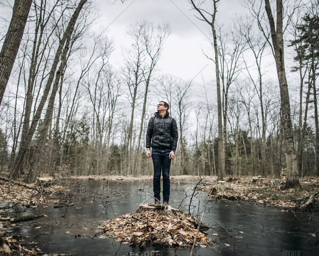 Tall man stands on stump in middle of swamp on cold cloudy day