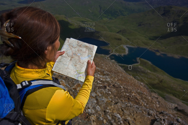 Woman reading a map on Snowdonia mountain