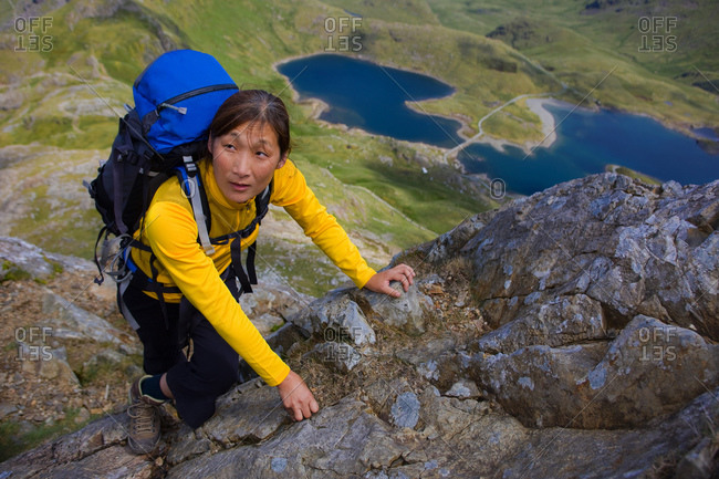 Woman with rucksack scrambling up Snowdonia mountain