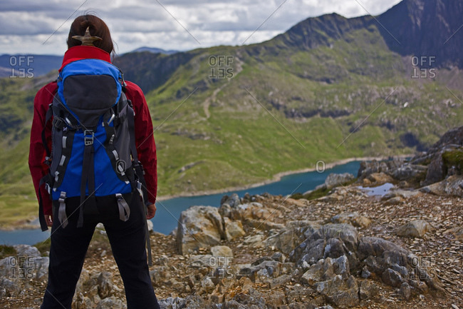 Woman with rucksack overlooking a mountain lake on Snowdonia