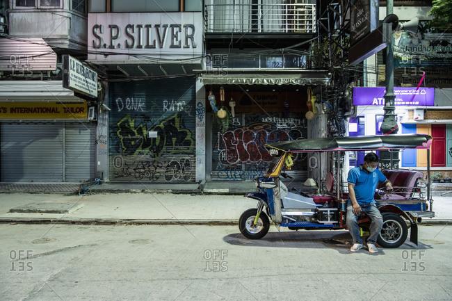 Bangkok, Bangkok, Thailand - April 2, 2020: Tuk Tuk driver at deserted Khaosan Road in Bangkok during Covid 19