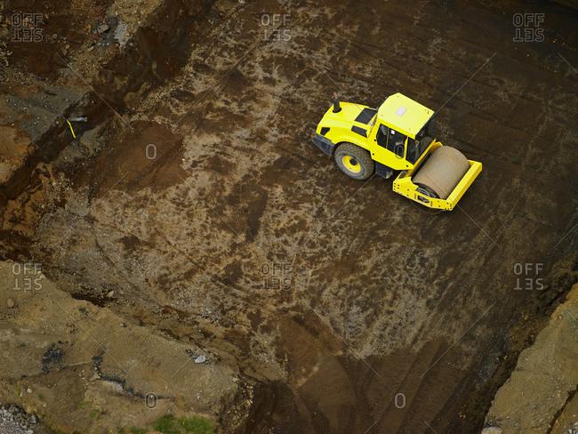 Aerial shot of steamroller preparing a building plot in Iceland