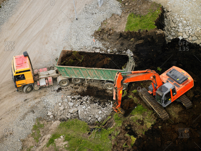 Aerial shot of earth mover filling dump truck at building site
