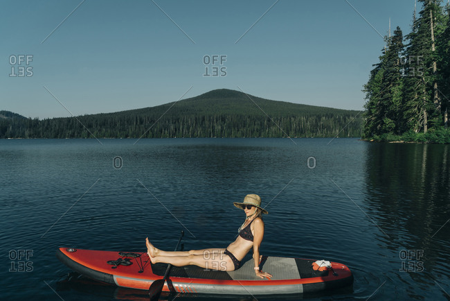 A young woman sits on a SUP on Lost Lake in Oregon.