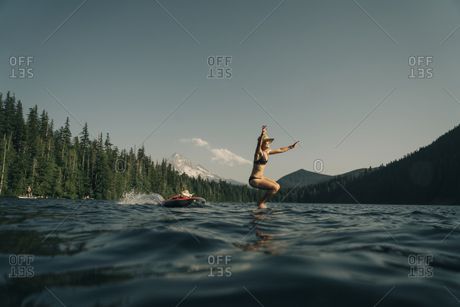 A young woman jumps from a paddle board into Lost Lake in Oregon.
