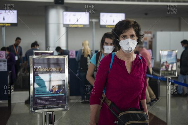 Khajuraho, MP, India - March 16, 2020: Middle aged woman wearing a face mask walking by a Coronavirus warning at an airport.