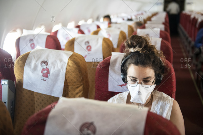 Khajuraho, MP, India - March 14, 2020: Young woman wearing a face mask while she listens to music on an almost empty plane, consequence of the Coronavirus pandemic of 2020.