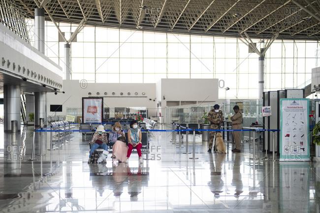 Khajuraho, MP, India - March 16, 2020: Asian passengers wearing face masks waiting at a deserted airport due to the health crisis caused by Coronavirus in Kajuraho, Madhya Pradesh, India.