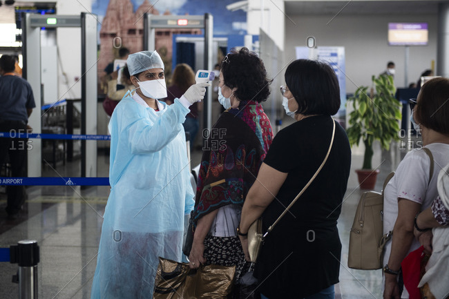 Khajuraho, MP, India - March 16, 2020: Health staff scanning asian passengers for possible symptoms of Coronavirus before they board their plane at the Khajuraho airport, Madhya Pradesh, India.