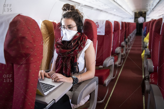 Khajuraho, MP, India - March 14, 2020: Young woman wearing a face mask while she works on an almost empty airplane due to the travel concerns and restrictions caused by the Covid-19 pandemic.