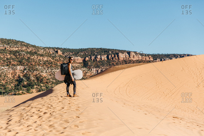 Woman with sand surfboard exploring coral pink sand dunes in Utah