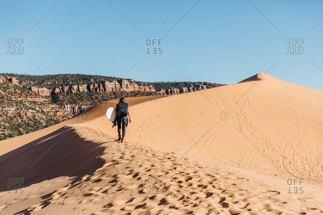 Woman with sand surfboard walking along on coral pink sand dunes