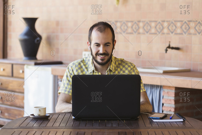 Smiling man working from home with a laptop computer