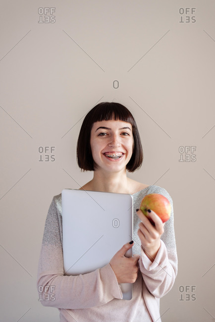 Portrait of young student, holding files and laptop