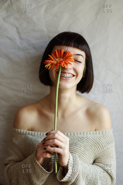 Studio portrait of a young beautiful woman with a flower in front of her face