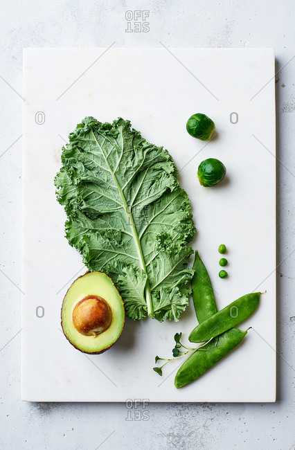 Flat lay with kale, avocado and peas on marble