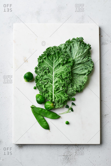 Flat lay with kale, brussel sprouts and peas on marble