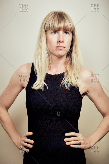 Blonde woman wearing a black dress posing without makeup