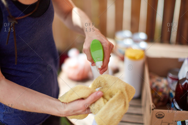 Woman spraying disinfectant on a cloth in preparation to clean her groceries during the Covid-19 outbreak