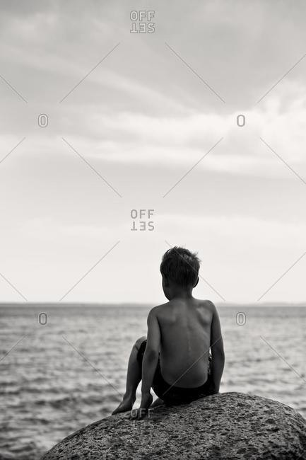 Boy sitting on a rock by the sea, Sweden