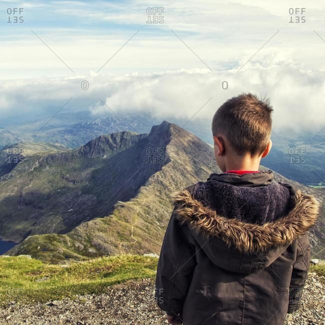 Rear view of a boy looking at mountain landscape, Snowdonia, Wales, UK