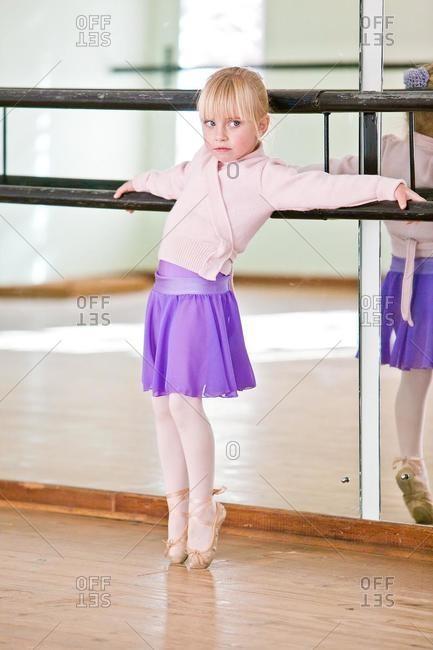 Girl leaning against barre in ballet studio