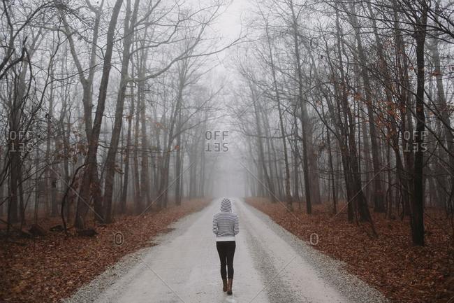 Rear view of woman walking along treelined road, Tennessee, USA