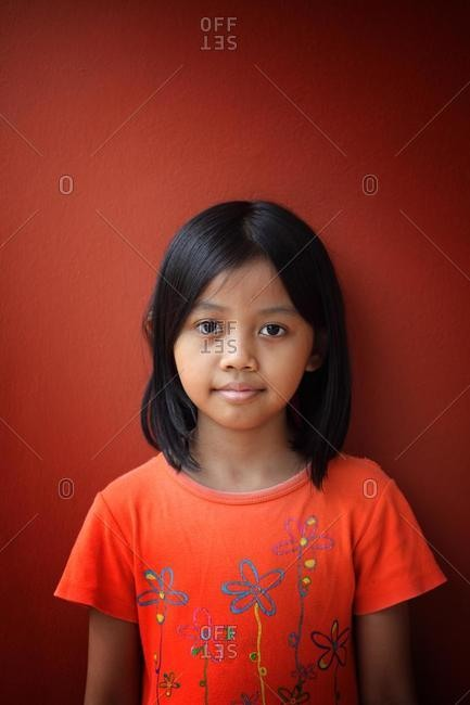 Portrait of girl standing in front of red wall