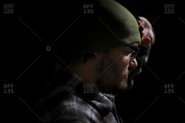 Profile of a depressed man with his hand on his head
