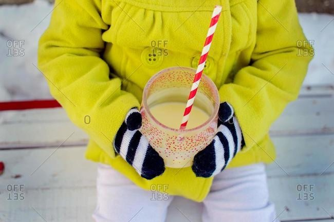 Close-up of a girl sitting outdoors in winter holding a milkshake