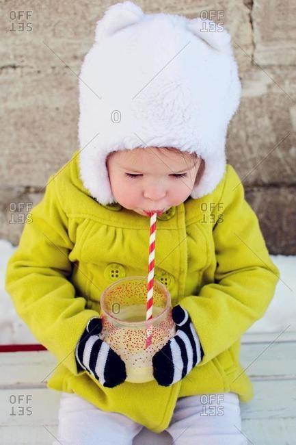 Girl sitting outdoors in winter drinking a milkshake