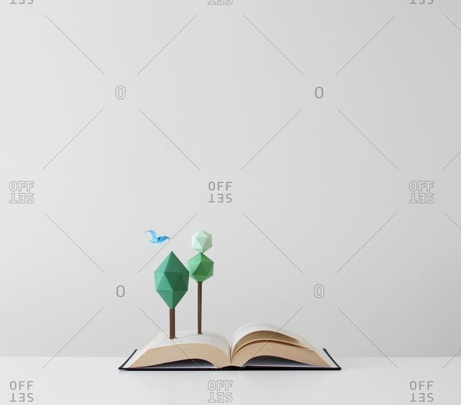 Trees and bird growing out of an open pop-up book