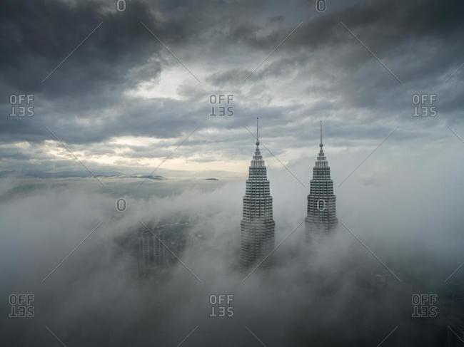 April 9, 2020: Petronas Twin Towers through low clouds, Kuala Lumpur, Malaysia