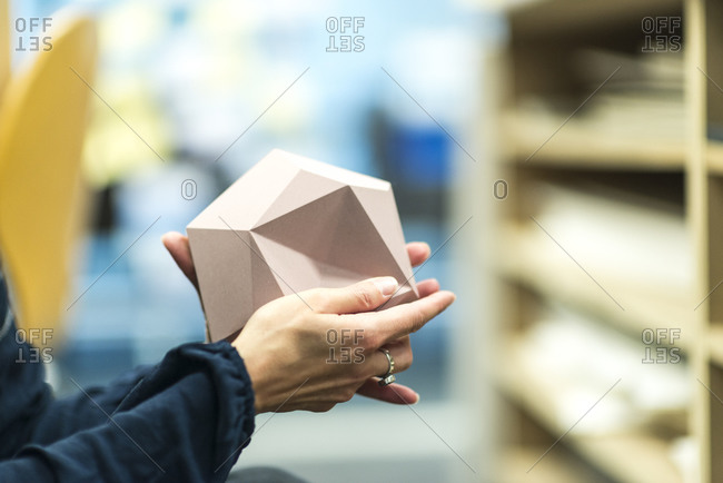 An interior designer holds a three dimensional tile in her hands