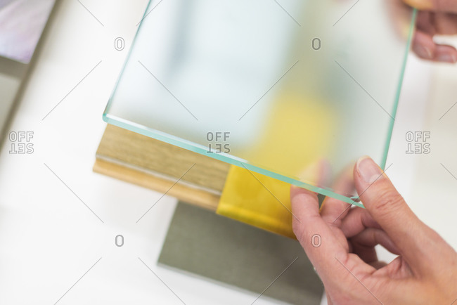 An interior designer looks at a glass tile