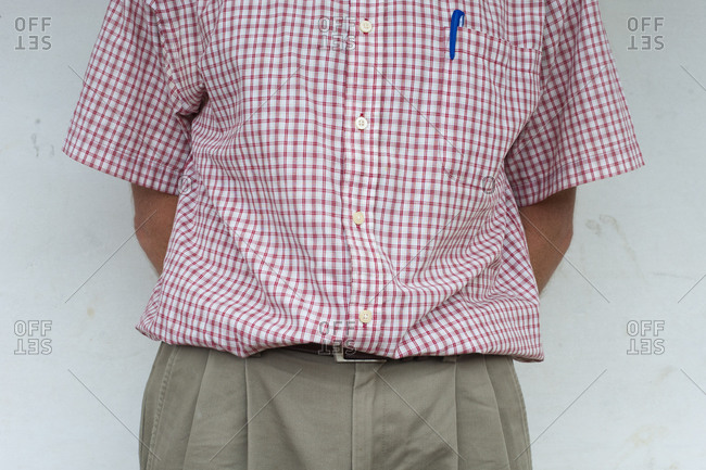 A man wearing a shirt and trousers with a pen in his pocket stands with his hands behind his back