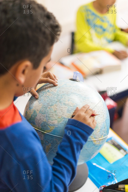 Boy looking at a globe in a classroom