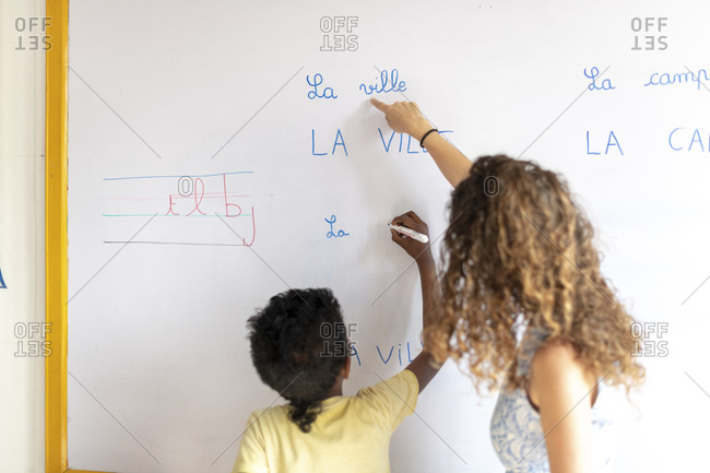 Kathmandu, Nepal - March 4, 2019: A teacher in a school in Kathmandu helps a child write French words on a whiteboard