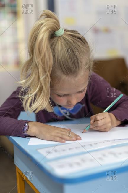 Kathmandu, Nepal - March 4, 2019: A girl at a school in Kathmandu writes in her exercise book
