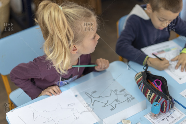 Kathmandu, Nepal - March 4, 2019: A girl at a school in Kathmandu draws a picture of a shark with a pencil