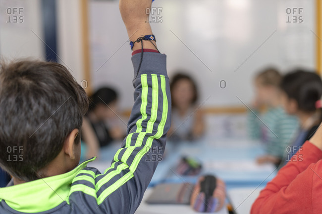 Kathmandu, Nepal - March 4, 2019: A boy at a school in Kathmandu holds up his hand to ask the teacher a question