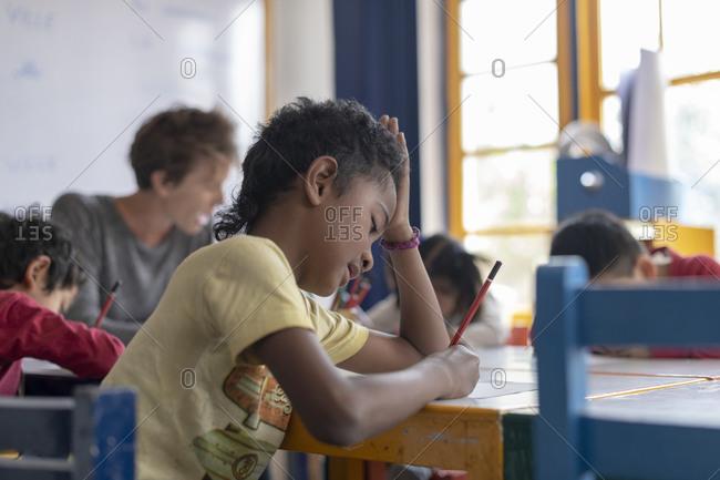 Kathmandu, Nepal - March 4, 2019: A boy strains to understand questions in a text in a school in Kathmandu