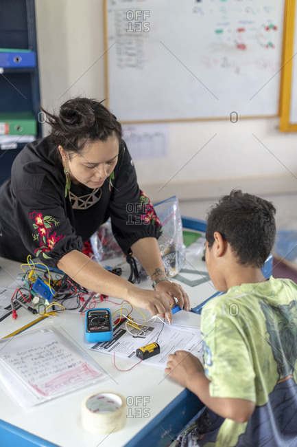 Kathmandu, Nepal - March 4, 2019: A teacher in a school in Kathmandu helps students with their work in a science and technology class