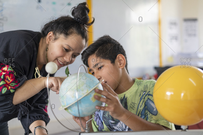 Kathmandu, Nepal - March 4, 2019: A teacher in a school in Kathmandu helps a student understand the world by pointing to countries on a globe