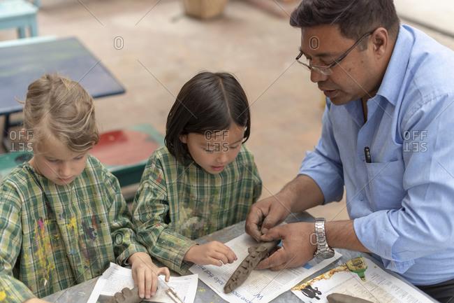 Kathmandu, Nepal - March 4, 2019: A teacher in a school in Kathmandu helps children make a crocodile with modelling clay