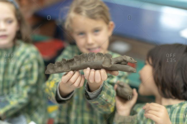Kathmandu, Nepal - March 4, 2019: A girl holds up a model of a crocodile she has made from clay in a school in Kathmandu