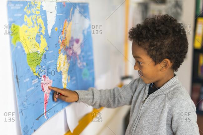 Kathmandu, Nepal - December 12, 2015: A boy points to Brazil on a map of the world on the wall in a school in Kathmandu